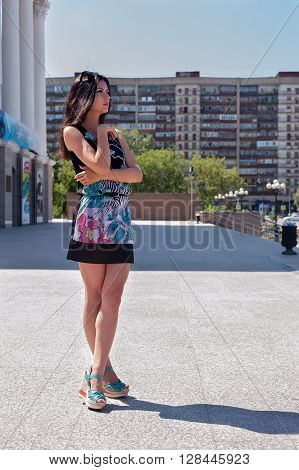 Beautiful young girl in dress over city background