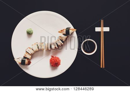 Japanese food restaurant, unagi sushi and roll plate set. One portion. Sushi unagi, chopsticks, ginger and wasabi. Sushi at white round plate, black background. Top view, soy sauce.