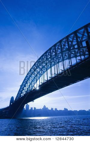 Sydney Harbour Bridge at dusk with view of distant skyline and harbour in Sydney, Australia.