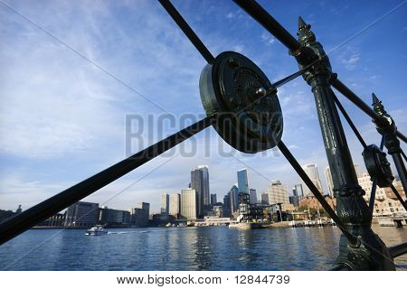 View of Sydney Cove from behind decorative iron railing with city skyline and water in Sydney, Australia.