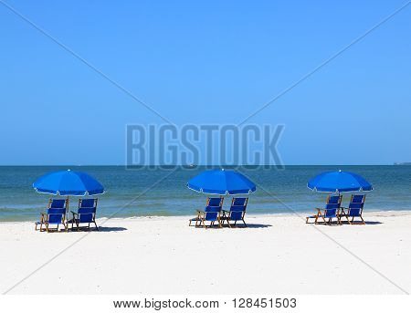 FORT MYERS BEACH, USA - MAY 12, 2015: Blue beach chairs and blue sunshades on the beach in Fort Myers Beach viewing the Gulf of Mexico.