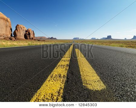 Open highway in scenic desert landscape with distant mountains and butte land formations.