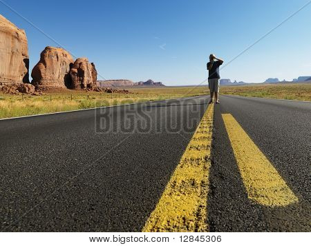 Caucasian teenage boy standing in open road in desert with landforms taking photograph.