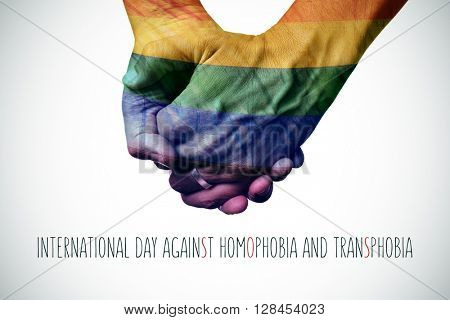 closeup of a gay couple holding hands patterned as the rainbow flag and the text international day against homophobia and transphobia