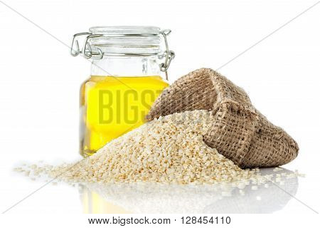 Sesame oil in a transparent glass jug and sesame close-up isolated on white background