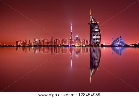 DUBAI, UAE - APR 11, 2013: Dubai skyline reflection at amazing night, Dubai, United Arab Emirates