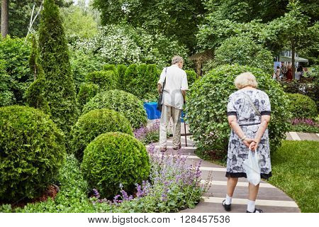 MOSCOW, RUSSIA - JUN 26, 2015: Senior people walk in Sokolniki park. Park founded in 1878 in hunting area of Russian kings near Moscow.