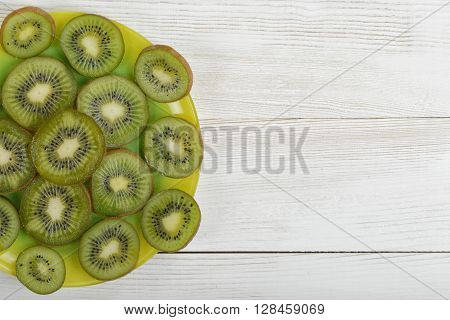 Dish full of kiwi slices on wooden surface with copy space. Top view composition. Helping digestion with enzymes. Boosting immunity. Creating alkaline balance. Naturally organic food. Premier Antioxidant Protection.