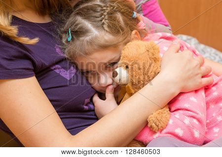 Little Girl With A Teddy Bear Clung To Her Mother With A Sad Expression On His Face