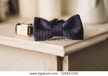 Classic groom accessories: blue bow tie and watch on a wooden table. Set of men's stylish vintage clothing. Male decoration for couple. Jewelry for man. Groom's morning.