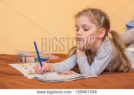 Little Girl Studying A Magazine With A Pencil In His Hand Lying On His Stomach And His Head In His S