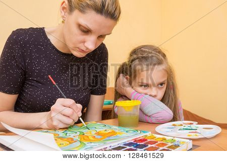 The Girl-artist Draws On The Colors Of Paper Next To A Little Girl With A Bored Look