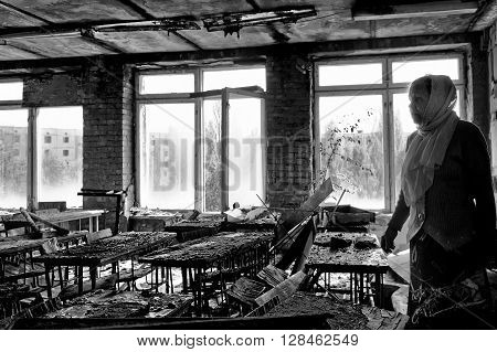 Pripyat, Ukraine - May 9, 2011: Evacuated teacher stands in her former classroom in abandoned school in Pripyat town in Chernobyl Exclusion Zone, place of Chernobyl nuclear disaster.