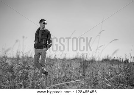 Monochrome photo of young fashionable man with sunglasses and windbreaker standing outdoor. There is a  field as background.