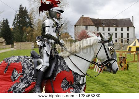 Harcourt France - April 23 2016: An unidentified man in a suit of armour is riding his horse to a mediaeval jousting tournament on Apr. 23 2016 in Harcourt France. It takes place in front of the castle Harcourt in Harcourt France