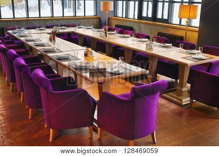RUSSIA, MOSCOW - DEC 28, 2014: Hall with served tables with plate Reserved and violet soft armchairs in restaurant Siren (Lilac) in Sokolniki park.