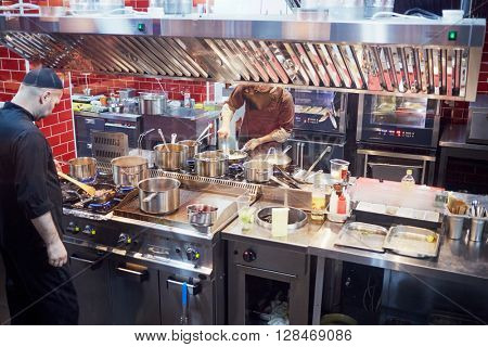 RUSSIA, MOSCOW - DEC 28, 2014: Cooks in the kitchen prepare food in the restaurant Siren (Lilac), located in Sokolniki park at Pesochnaya alley.