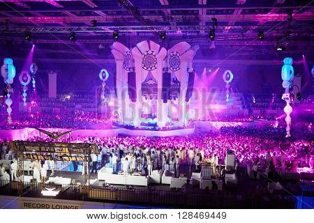 RUSSIA, MOSCOW - JUN 12, 2015: Central stage and dancing people on dance floor around and at grandstands and lounges during Sensation Wicked Wonderland show at Olympiysky sports complex.