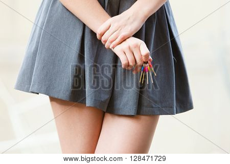 Safety access fashion concept. Young girl holding keyring. Youthful lady in skirt keeping keys.