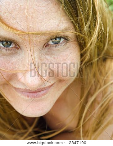 Close up portrait of attractive redheaded woman looking at viewer.