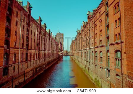 Large river canal with bricks buildings on the sides, sun and shadow, color mix.