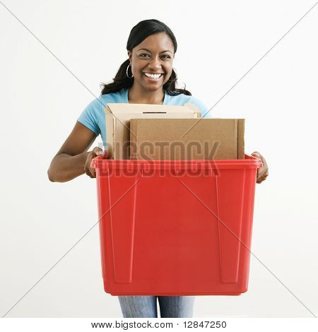 African American young adult female holding recycling bin with cardboard in it.