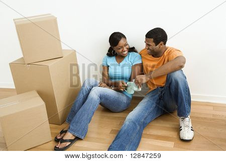 African American male and female couple sitting on floor next to moving boxes relaxing.
