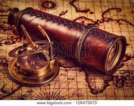 Travel geography navigation concept background - vintage retro effect filtered hipster style image of old vintage retro compass with sundial and spyglass on ancient world map