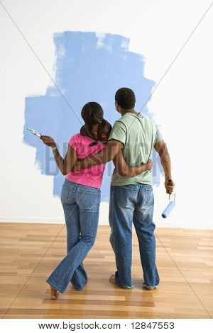 African American couple standing together looking at half-painted wall.