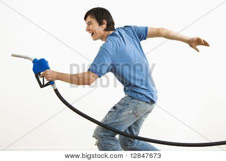 Asiatische junger Mann, mit dem Ziel Benzin Pumpe Düse wie ein Gewehr.