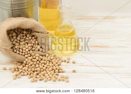 Soybean in hemp sack bag with oil in laboratory glass setup on wooden table.