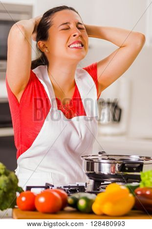 Young woman chef holding hair in frustration, discouraged facial expression, table with kettle and vegetables.