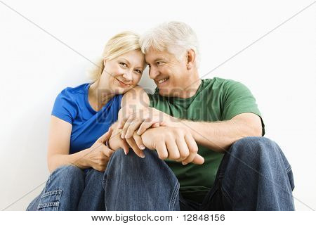 Middle-aged couple sitting together smiling.