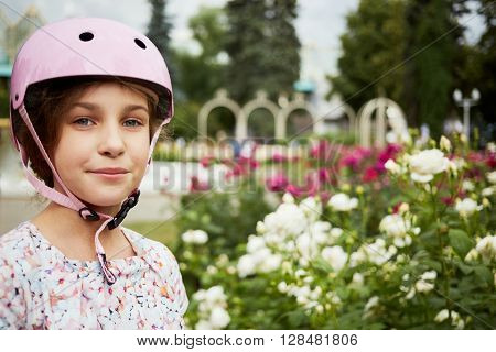 Little girl in protective pink helmet stands against flowerbed, humeral portrait.