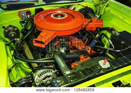 V-8 engine in a classic hot rod painted orange with chrome headers.