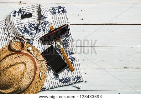Overhead view of men's casual outfits Outfits of traveler boy male Men's casual outfits on wood board background Summer items for men traveler poster
