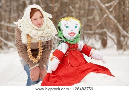 Teenage girl stands and lloks at stuffed dummy Maslenitsa, sitting on snowbank in winter park.