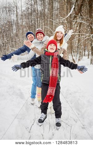 Happy family of four stands on skates on ice pathway in winter park spreading arms to sides.