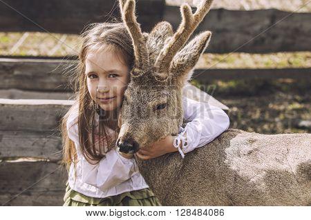 Beautiful Little Girl Hugging Animal Roe Deer In The Sunshine