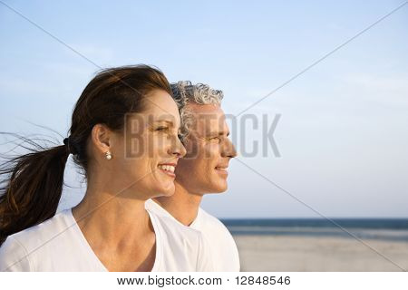 Side view of smiling middle aged couple on beach looking off into the distance together. Horizontal shot.