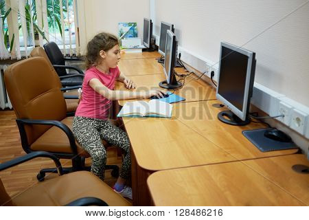 Little girl sits alone at table with computer monitor at computer room.