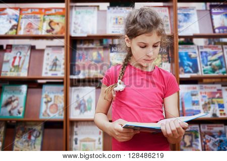 Little girl stands reading book in the hall of library with many bookshelves.