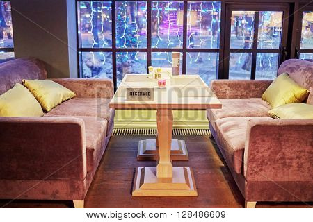 Table with plate Reserved and two sofas near window in cafe.