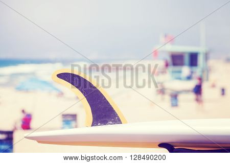 Vintage toned surfboard fin with lifeguard tower in distance shallow depth of field Venice Beach USA.