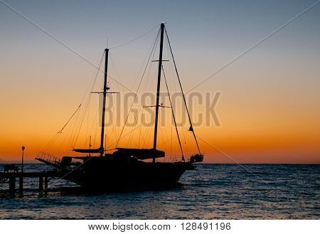 Seascape with Small Sailing Ship and Pier Early Morning on Sunrise Sky background Outdoors
