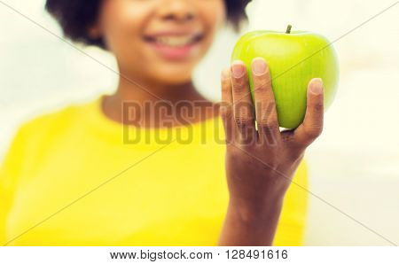 people, food, healthy eating and dental care concept - close up of happy african american young woman with green apple at home