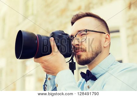 people, photography, technology, leisure and lifestyle - happy young hipster man holding digital camera with wide angle lens taking picture on city street