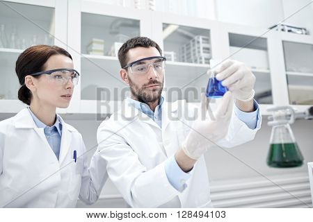 science, chemistry, technology, biology and people concept - young scientists with glass flask or test tube making research in clinical laboratory