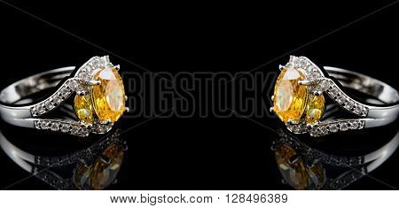 Silver or white gold rings with yellow gems and diamonds on black glass background with space for your text