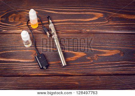 electronic nicotine inhalator on  background ,bottles with liquids behind the inhalator